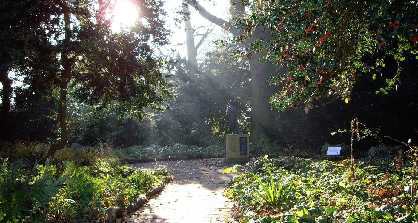 Path through the woods, with The First Undergraduate statue