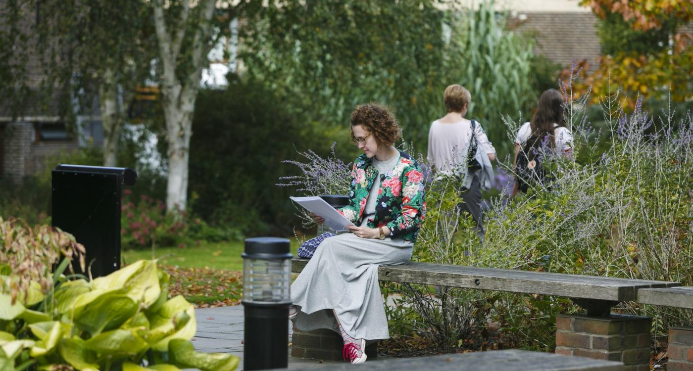 girl sitting on a bench reading